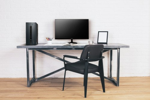 Modern black chair at designer desk with blank white computer screen and picture frames. Mock up
